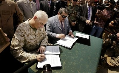 U.S. Marine Maj. Gen John Kelly, the top U.S. commander in Anbar Province, left, and Anbar Governor Maamoun Sami Rashid, center, sign papers during a handover ceremony at the government headquarters in Ramadi, capital of Anbar province, in Iraq Monday, Sept. 1, 2008