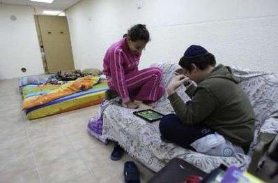 Israeli children huddle in a bomb shelter in town of Sderot