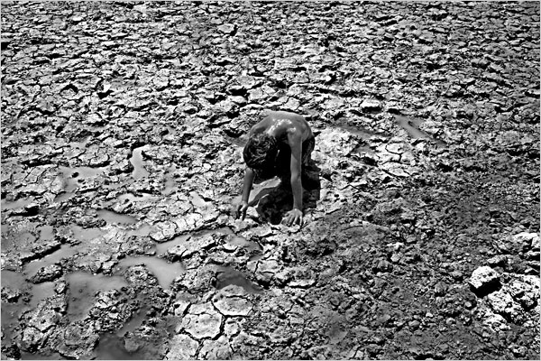 "NYT caption: ""A boy rested on the mud in a dried-up section of the Euphrates River near Jubaish, Iraq, in June."""