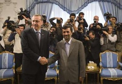 Closer than ever: Turkish PM Tayyip Erdogan shakes hands with Ahmadinejad on state visit to Tehran.