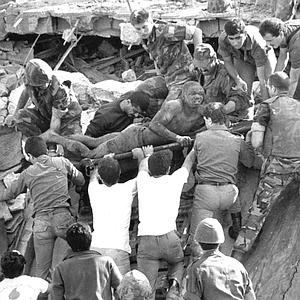 """British soldiers give a hand in rescue operations at the site of the bomb-wrecked U.S. Marine command center near Beirut airport Sunday, Oct. 23, 1983.  A bomb-laden truck drove into the center collapsing the entire four story building."" (AP Photo/Bill Foley)"