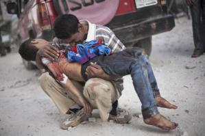 """""""A son is meant to bury his father, but here a Syrian man cries while holding the body of his son near Dar Al Shifa hospital in Aleppo, killed by the Syrian Army."""" (photo credit: Manu Brabo, AP)"""